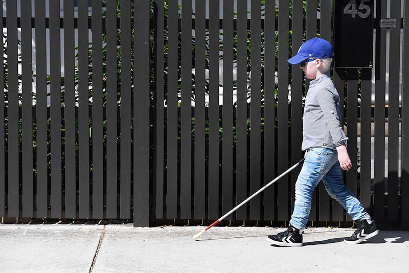 Jasper walking along the footpath using a white cane